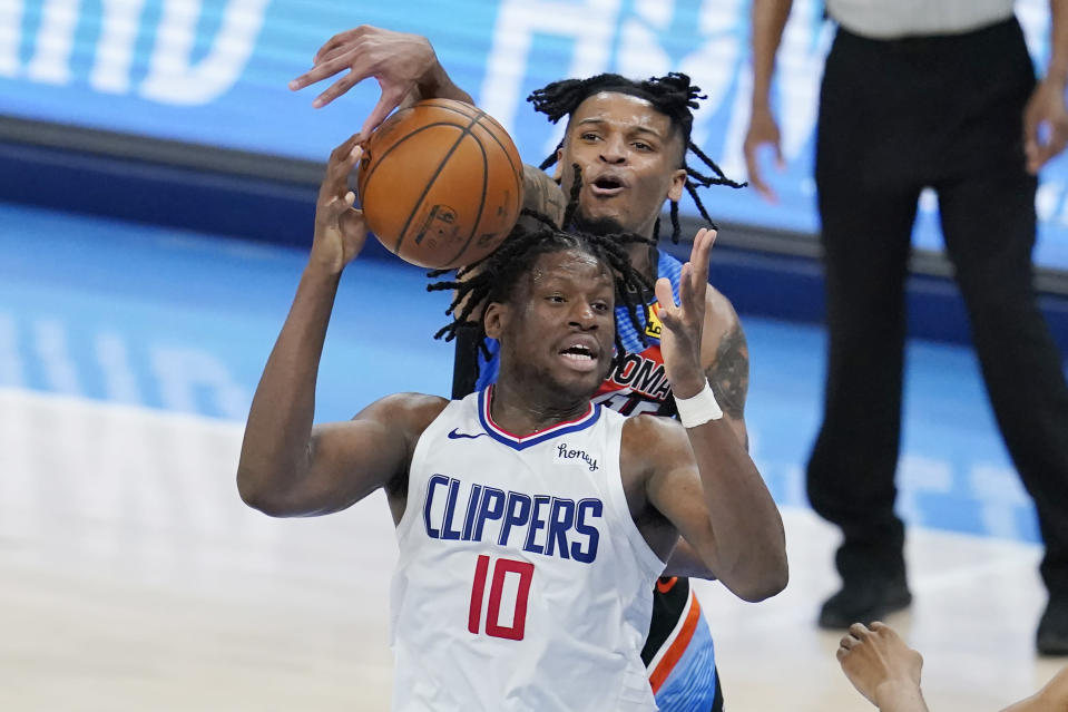 Oklahoma City Thunder forward Josh Hall, rear, tries to knock the ball away from Los Angeles Clippers center Daniel Oturu (10) in the second half of an NBA basketball game Sunday, May 16, 2021, in Oklahoma City. (AP Photo/Sue Ogrocki)