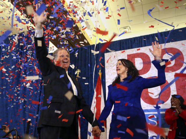 Doug Jones and his wife, Louise Jones, wave to supporters before speaking in Birmingham, Ala., at a victory party on election night. (Photo: John Bazemore/AP)