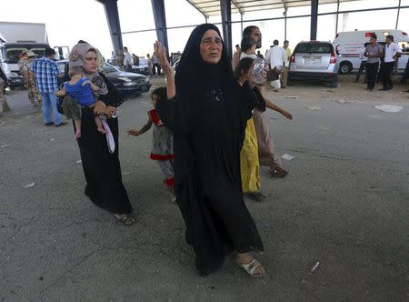A woman reacts as families fleeing the violence in the Iraqi city of Mosul arrive at a checkpoint on the outskirts of Arbil, in Iraq's Kurdistan region June 10, 2014. REUTERS/Stringer