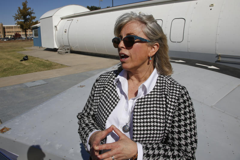 Stacey L. Zinke-McKee, a medical-research official at the Federal Aviation Administration facility in Oklahoma City, answers a question in front of an aircraft simulator Thursday, Oct. 17, 2019, in Oklahoma City. Federal researchers, using 720 volunteers in Oklahoma City, will test whether smaller seats and crowded rows slow down airline emergency evacuations. (AP Photo/Sue Ogrocki)