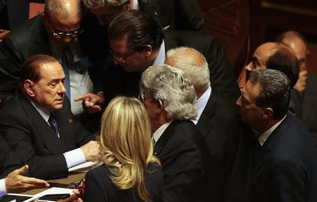 Italian center-right leader Berlusconi talks with senators at the Senate after PM Letta's asking for possible call for confidence vote immediately in Rome
