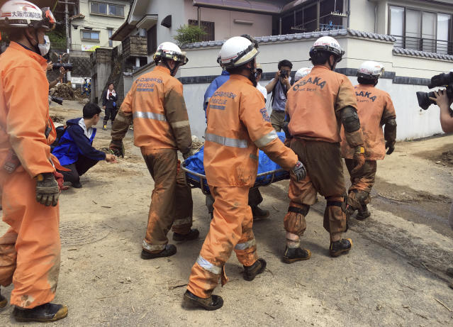 <p>Emergency rescue teams recover the body of a victim in the heavy rains, July 9, 2018, in Hiroshima, Japan. (Photo: Haruka Nuga/AP) </p>
