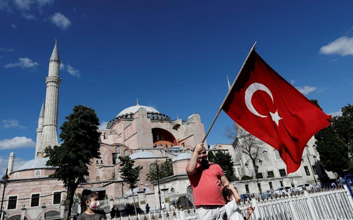 A man waves a Turkish Flag in front of the Hagia Sophia after the court decision - REUTERS/Murad Sezer