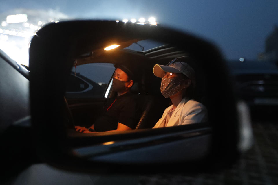 People sit in their car as they watch the Stage X drive-in concert at KINTEX parking lot in Goyang, South Korea, Saturday, May 23, 2020. The concert's aim is to provide entertainment for South Korean citizens who have been craving for music events that have been suspended during the coronavirus outbreak. (AP Photo/Ahn Young-joo)