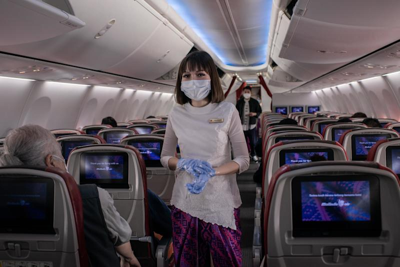 HONG KONG INTERNATIONAL AIRPORT, HONG KONG, CHINA - 2020/02/14: An airline staff member wears surgical mask inside an airplane at the Hong Kong International Airport. As the number of victims of the new Coronavirus increases, more countries cancel flights within and without the region. (Photo by Ivan Abreu/SOPA Images/LightRocket via Getty Images)