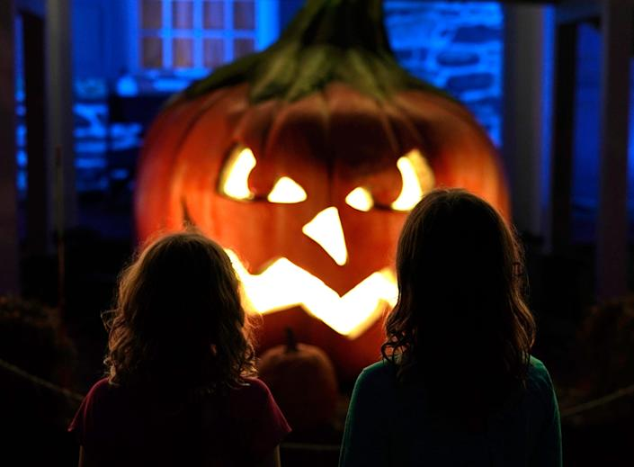 Children look at scary Halloween pumpkin carving.