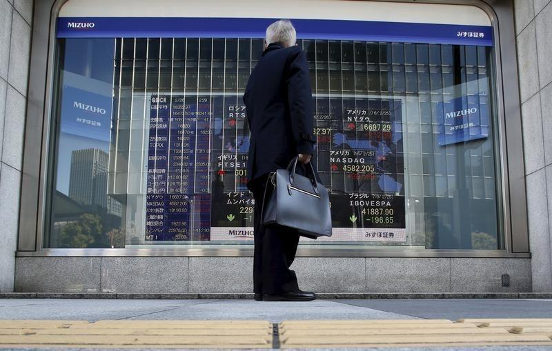 A pedestrian stands to look at an electronic board showing the stock market indices of various countries outside a brokerage in Tokyo