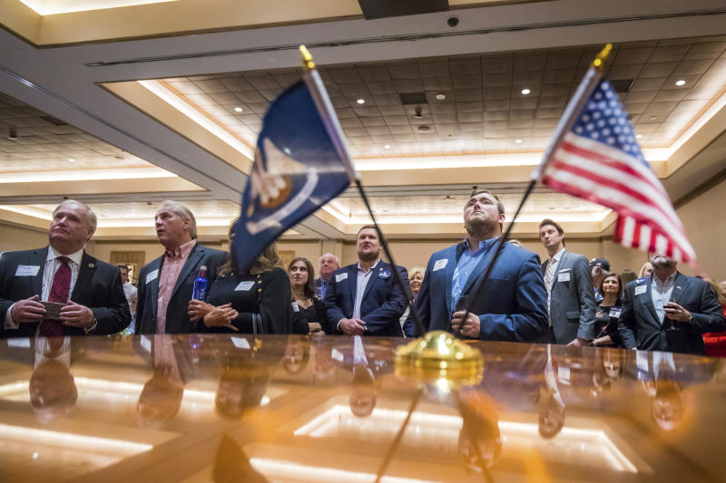 Louisiana Republican gubernatorial candidate Eddie Rispone fans watch returns on a projector during the Rispone election night watch party at L'Auberge Casino and Hotel in Baton Rouge, La., Saturday, Nov. 16, 2019. (AP Photo/Sophia Germer)