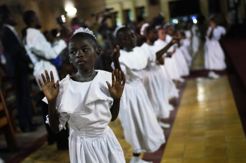 """Congolese children dance before Msg. Fridolin Ambongo, the the newly appointed Archibishop of Kinshasa, delivers the homily during an early midnight mass at the Notre Dame du Congo Cathedral in Kinshasa, Congo, Monday Dec. 24, 2018. Ambobgo said that Congolese people must embrace non-violence to make it through Dec. 30th elections. He warned that """"The publication of results that would not reflect the will of the people as expressed in the ballot boxes would mean the annihilation of peace in our country. """" (AP Photo/Jerome Delay)"""