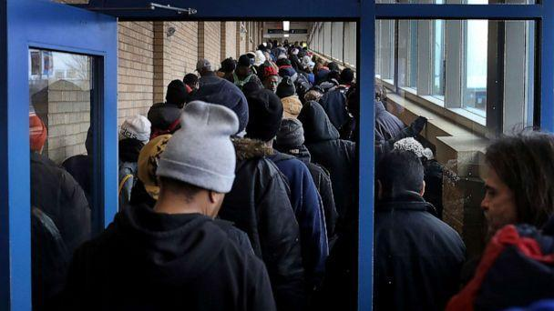 PHOTO: For some social distancing works, for the poor and homeless, getting food to eat doesn't always allow that as evidenced by the line for lunch at Sharing & Caring Hands, March 24, 2020, in Minneapolis. (David Joles/Star Tribune via AP)