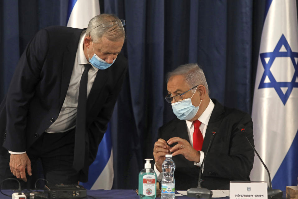 "FILE - In this June 7, 2020 file photo, Israeli Prime Minister Benjamin Netanyahu, right, speaks with Defense Minister Benny Gantz, both wearing protective mask due to the ongoing coronavirus pandemic during the weekly cabinet meeting in Jerusalem. When Netanyahu and his rival, Gantz, agreed to form an ""emergency"" government in May after three bitter, and ultimately deadlocked, election campaigns, the goal was to stabilize Israeli politics in the face of a global pandemic. Less than 100 days later their fractious coalition government appears to be headed toward collapse as Israel grapples with a raging coronavirus outbreak, an economic calamity and a wave of public protests. (Menahem Kahana/Pool Photo via AP, File)"