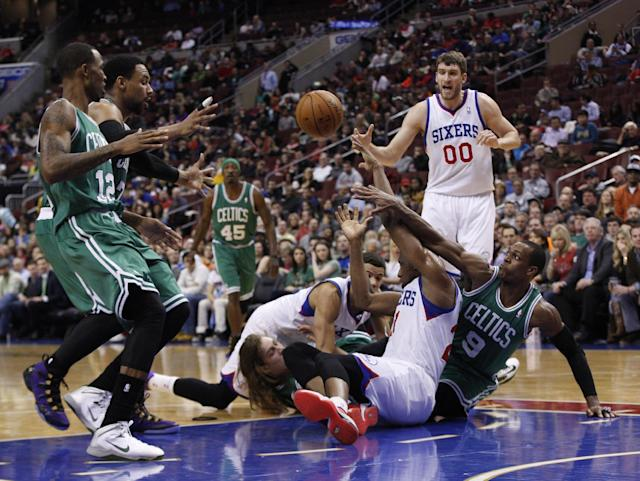 Philadelphia 76ers' Thaddeus Young, center right, passes the ball from the floor while Boston Celtics' Rajon Rondo reaches from behind during the first half of an NBA basketball game, Wednesday, Feb. 5, 2014, in Philadelphia. (AP Photo/Chris Szagola)