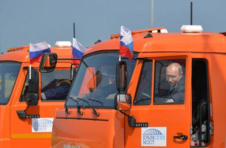 Russian President Vladimir Putin closes the door of a Kamaz truck during a ceremony opening a bridge, which was constructed to connect the Russian mainland with the Crimean Peninsula, near the Taman Peninsula in Krasnodar Region, Russia May 15, 2018. Sputnik/Alexei Druzhinin/Kremlin via REUTERS