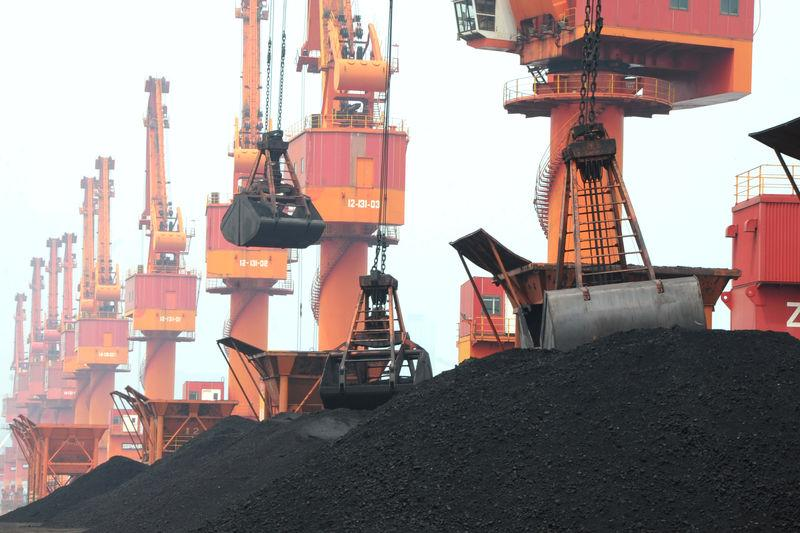 FILE PHOTO - Imported coal is unloaded by cranes from a coal cargo ship at a port in Lianyungang