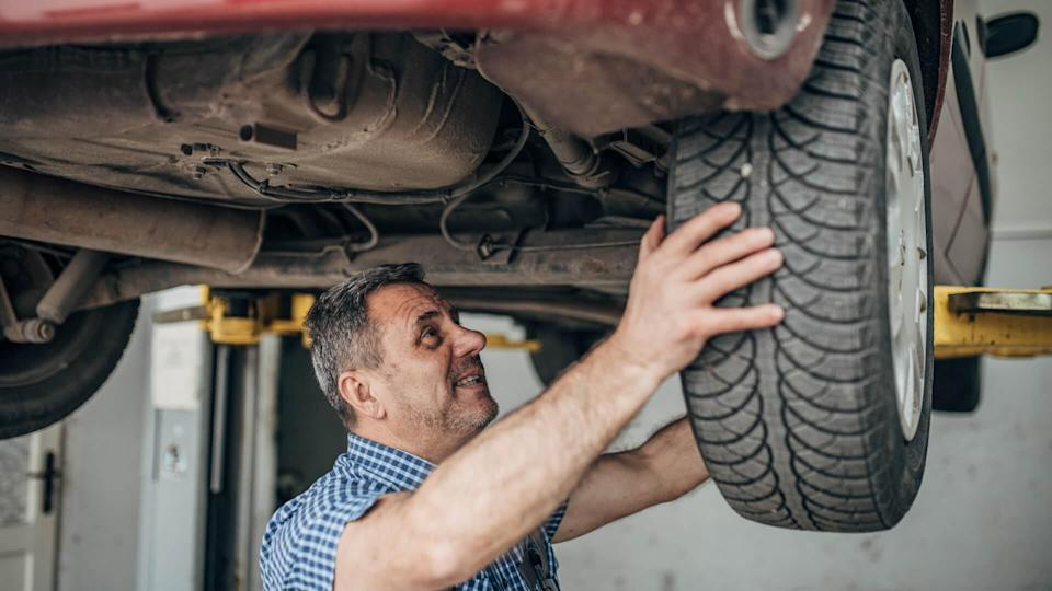 Auto mechanic repairing car at service, tire replacement.