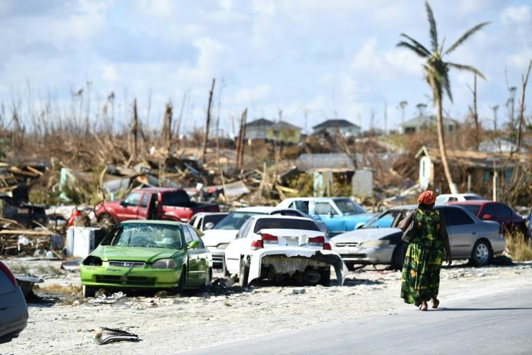 A woman walks by destroyed cars in The Mudd neighborhood of Marsh Harbour