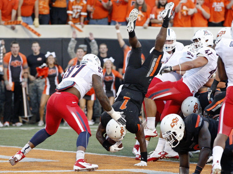 Oklahoma State running back Joseph Randle, center, goes up and over Arizona linebacker Paul Vassallo,(41), for a touchdown in the first quarter of an NCAA college football game in Stillwater, Okla., Thursday, Sept. 8, 2011.  Arizona's Mohammed Usman is at left. (AP Photo/Sue Ogrocki)