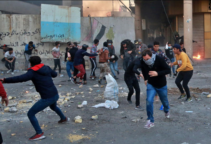 Anti-government protesters run for cover while security forces fire tear gas and live ammunition during clashes between Iraqi security forces and anti-Government protesters, in Baghdad, Iraq, Nov. 21, 2019. (Photo: Khalid Mohammed/AP)