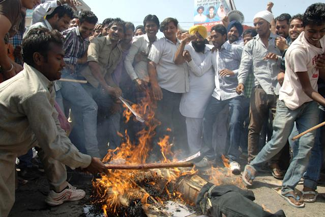 Indian villagers shout-slogans as they burn effigy of Pakistani government at Bikhiwind village, some 45 km from Amritsar on May 2, 2013. An Indian man on death row in Pakistan for spying died nearly a week after he was attacked by fellow prisoners, who were swiftly charged with murder as New Delhi demanded justice. Sarabjit Singh, who was sentenced 16 years ago over deadly bombings, died in the early hours as a result of the savage assault in Lahore's Kot Lakhpat jail, a senior doctor at Jinnah hospital in the eastern city told AFP. AFP PHOTO / NARINDER NANU (Photo credit should read NARINDER NANU/AFP/Getty Images)