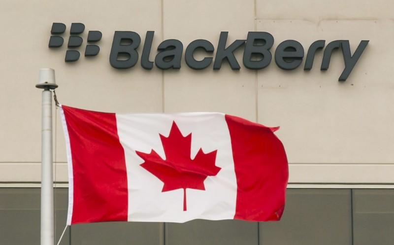 A Blackberry logo hangs behind a Canadian flag at their offices on the day of their annual general meeting for shareholders in Waterloo, Canada