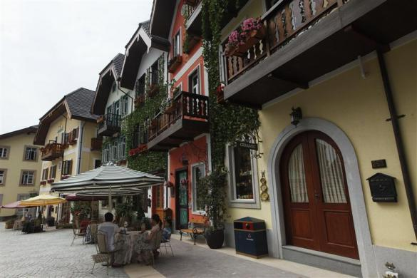 A family rests on the main street in the replica village of Austria's UNESCO heritage site, Hallstatt, in China's southern city of Huizhou in Guangdong province, June 1, 2012.