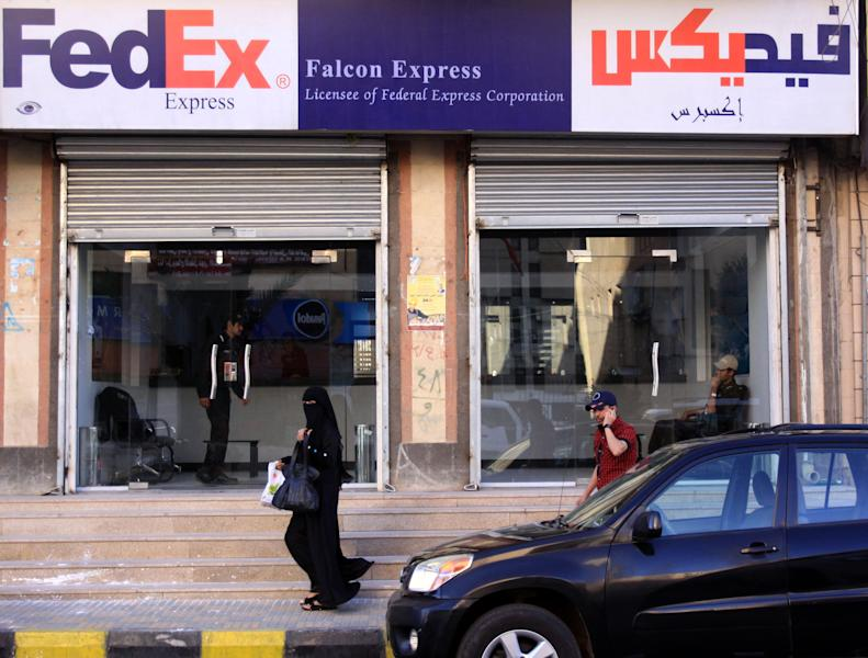 FILE - In this Saturday, Oct. 30, 2010 file photo, Yemenis walk past Falcon Express office, the partner service provider of FedEx in Sanaa, Yemen. After years of stalling under its now-ousted leader, Yemen is finally showing resolve in the fight against al-Qaida, aided by the United States, which just scored an intelligence coup by breaking up a new bomb plot there. (AP Photo/Hasan Jamali, File)