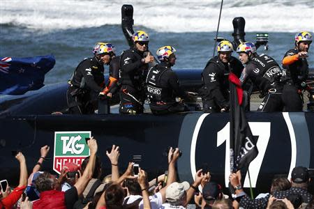 Oracle Team USA skipper James Spithill (3rd L) gives a thumbs up to spectators after the postponement of Race 13 of the 34th America's Cup yacht sailing race in San Francisco