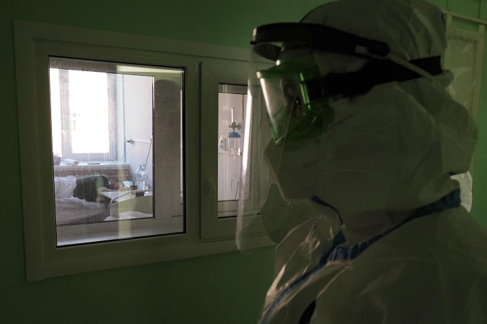 A medical worker walks into a coronavirus ward in a hospital in Sortavala, Karelia region, Russia, Tuesday, Feb. 16, 2021. Russia's rollout of its coronavirus vaccine is only now picking up speed in some of its more remote regions, although experts say the campaign is still moving slowly. (AP Photo/Dmitri Lovetsky)