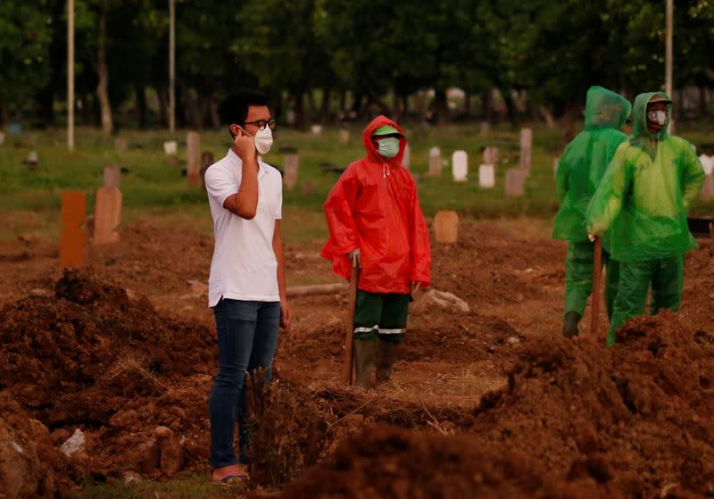 Firos Justin Sumantri, son of Ratih Purwarini, a doctor who passed away due to the coronavirus disease (COVID-19), prays as municipality workers wait, next to his mother's grave during the funeral in Jakarta