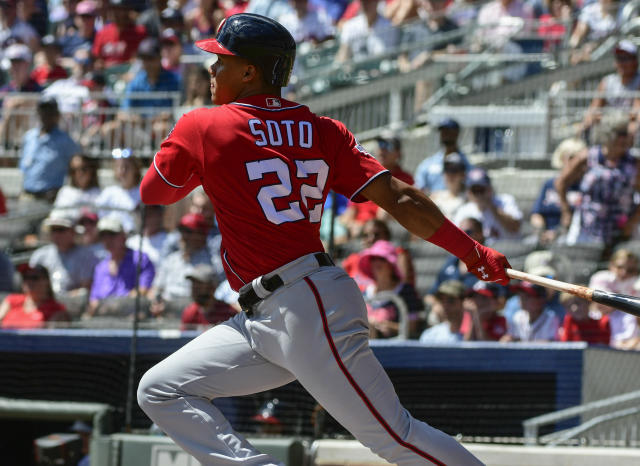 Washington Nationals' Juan Soto (22) hits a line drive single to centerfield during the first inning of a baseball game against the Atlanta Braves, Saturday, Sept. 15, 2018, in Atlanta. Bryce Harper scored on the play. (AP Photo/John Amis)