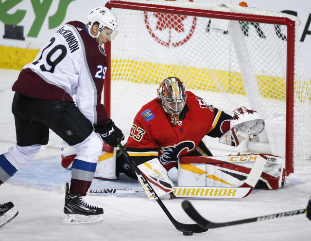 Colorado Avalanche's Nathan MacKinnon, left, tries to get the puck past Calgary Flames goalie David Rittich, of the Czech Republic, during the first period of an NHL hockey game Wednesday, Jan. 9, 2019, in Calgary, Alberta. (Jeff McIntosh/The Canadian Press via AP)