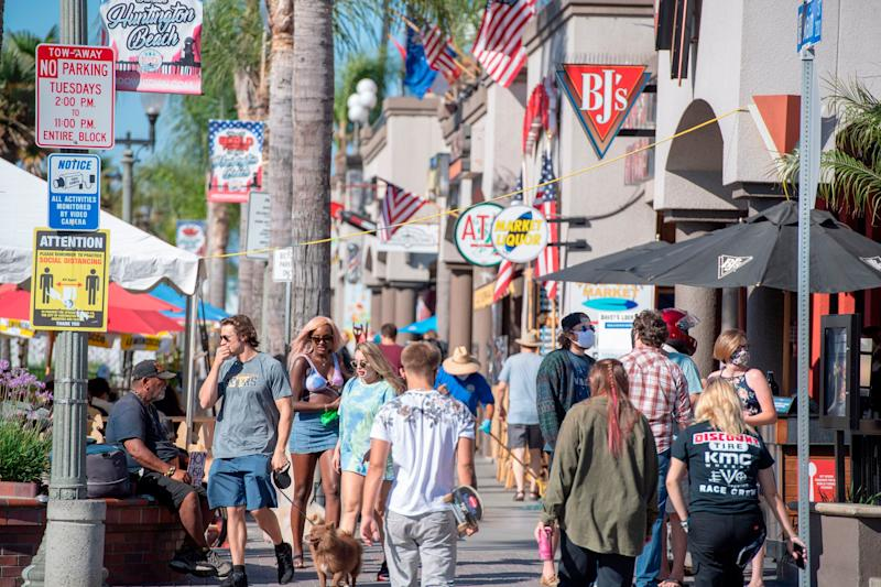 "Beachgoers, many maskless, walk down Main Street in Huntington Beach, California. Residents of the city south of Los Angeles have been notably <a href=""https://www.latimes.com/socal/daily-pilot/news/story/2020-06-30/huntington-beach-restaurants-no-mask-position-deeply-divides-o-c-diners"" target=""_blank"" rel=""noopener noreferrer"" data-ylk=""subsec:paragraph;itc:0;cpos:1;pos:3;elm:context_link"" data-rapid_p=""3"" data-v9y=""1"">anti-mask</a> and <a href=""https://timesofsandiego.com/politics/2020/05/01/thousands-many-without-masks-protest-lockdown-in-huntington-beach/"" target=""_blank"" rel=""noopener noreferrer"" data-ylk=""subsec:paragraph;itc:0;cpos:1;pos:4;elm:context_link"" data-rapid_p=""4"" data-v9y=""1"">lockdown-averse,</a> in spite of rising coronavirus cases in the region. (Photo: ROBYN BECK via Getty Images)"