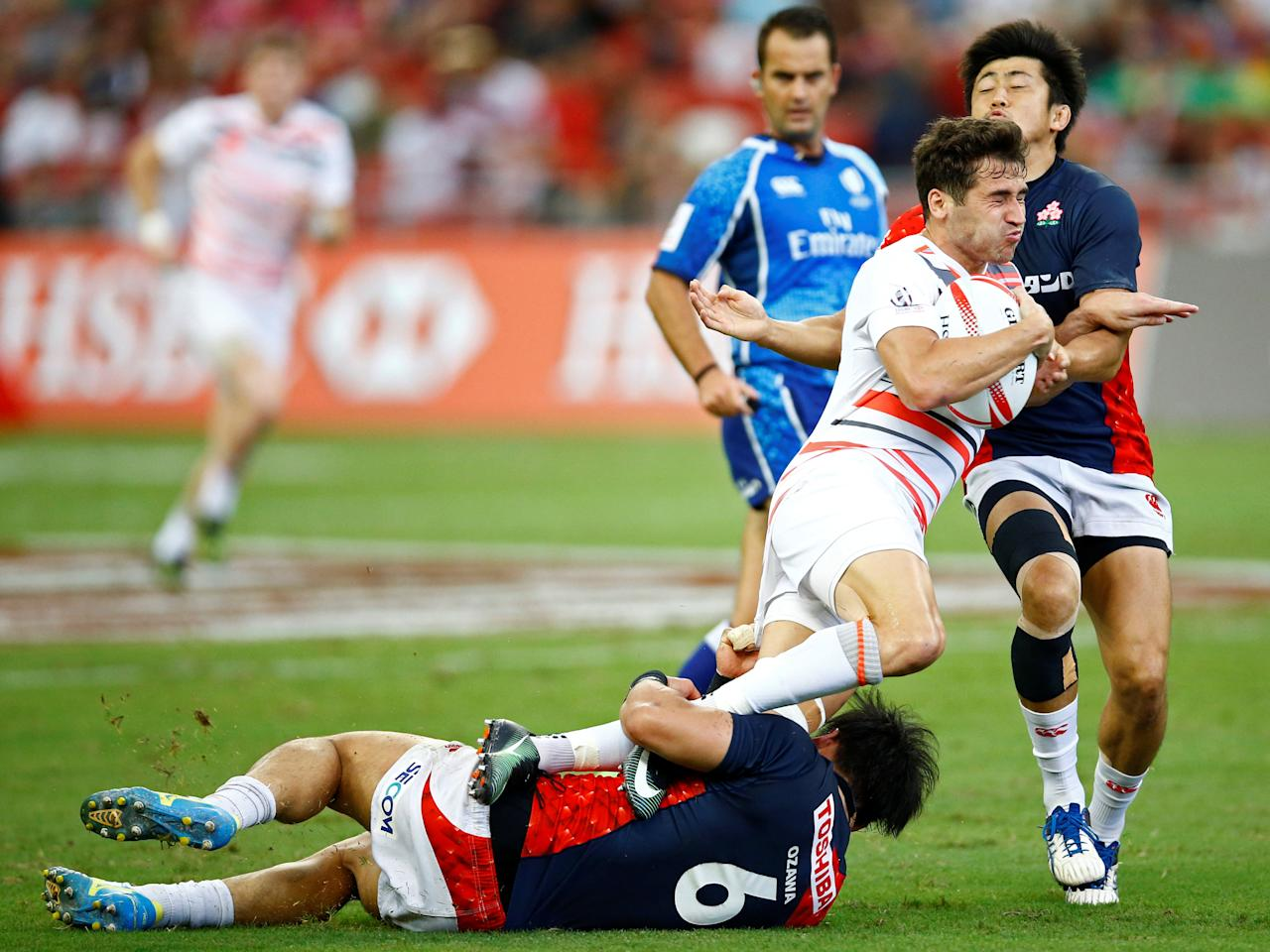 Rugby Union - Singapore Sevens - National Stadium, Singapore - 15/04/17 England's Oliver Lindsay-Hague is tackled by Japan's Dai Ozawa (L) and Kosuke Hashino. REUTERS/Yong Teck Lim