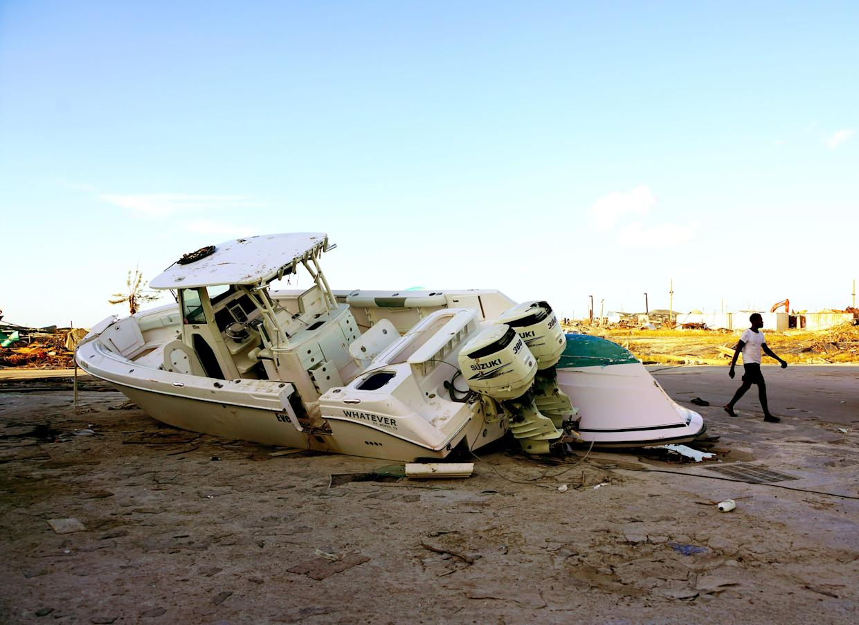 A Hurricane Dorian survivor walks past a beached powerboat in Marsh Harbour, Abaco Island, in the Bahamas on Sept. 5, 2019.