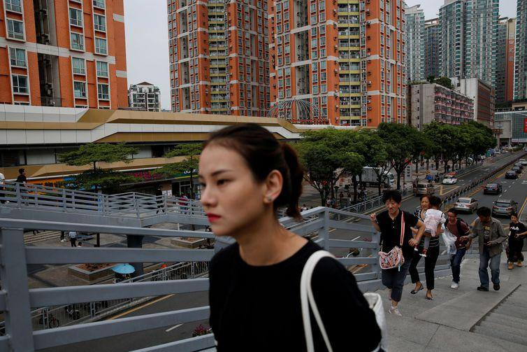 FILE PHOTO: People walk past newly built residential flats in Shenzhen, Guangdong Province, China October 26, 2019. REUTERS/Tyrone Siu/File Photo