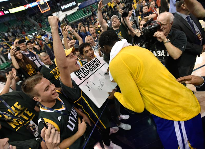 Draymond Green reviews, signs and initials a Jazz fan's very specific stat sheet. (Getty Images)
