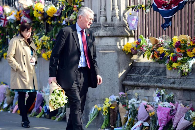 Touching tributes: Labour MP Hilary Benn passes floral tributes to the victims of the Westminster terrorist attack (Lauren Hurley/PA )