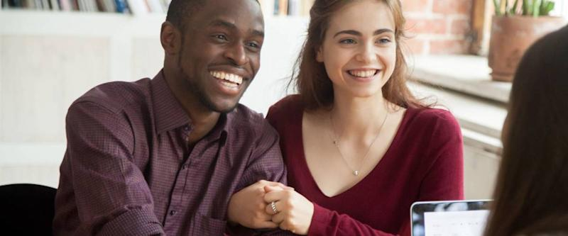 Smiling multiracial couple customers shaking hands with financial advisor