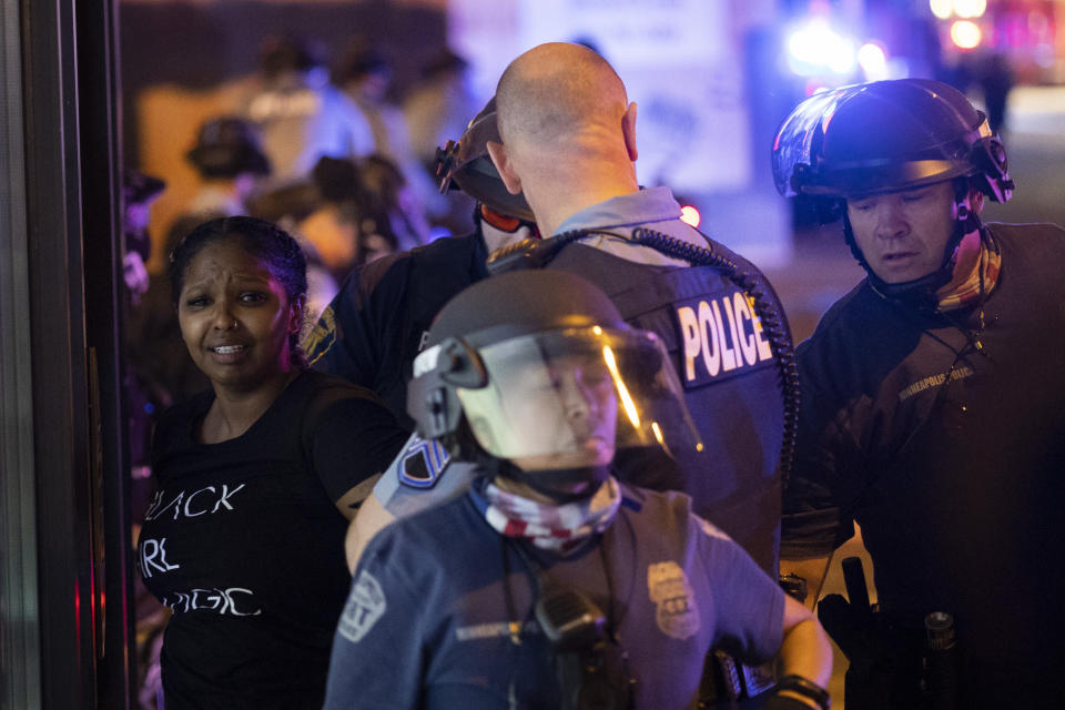 A protester is arrested by police after a vigil was held for Winston Boogie Smith Jr. early in Minneapolis on Saturday, June 5, 2021. Authorities said Friday that a man wanted on a weapons violation fired a gun before deputies fatally shot him in Minneapolis, a city on edge since George Floyd's death more than a year ago under an officer's knee and the more recent fatal police shooting of Daunte Wright in a nearby suburb. (AP Photo/Christian Monterrosa)