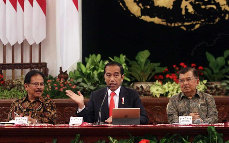 Indonesian President Joko Widodo (C) gestures next to Vice President Jusuf Kalla (R) and Minister of Agriculture and Land-Planning Sofyan Djalil (L) during a press conference about the new capital, at the presidential palace in Jakarta on August 26, 2019. | GAGAH ADHAPUTRA/Getty Images