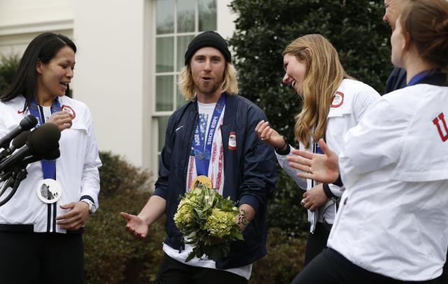 Olympic gold medalist Sage Kotsenburg speaks to reporters at the White House in Washington April 3, 2014. Flanking Kotsenburg are Julie Chu (L) and gold medalist Mikaela Shiffrin. U.S. President Barack Obama and first lady Michelle Obama will honor members of the U.S. teams and delegations from the Sochi Olympics and Paralympics at the White House today. REUTERS/Kevin Lamarque (UNITED STATES - Tags: POLITICS SPORT OLYMPICS)