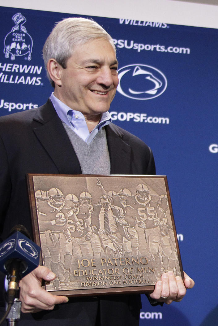 """FILE - In this Oct. 29, 2011 file photo, Penn State President Graham Spanier presents head football coach Joe Paterno with a plague commemorating his 409th collegiate win after an NCAA college football game against Illinois in State College, Pa. Spanier is accused of perjury, endangering children and other charges in the Jerry Sandusky molestation scandal. According to online court records charges were filed, Thursday, Nov. 1, 2012, against Penn State's ex-president and two other administrators in what prosecutors called """"a conspiracy of silence."""" (AP Photo/Gene J. Puskar)"""