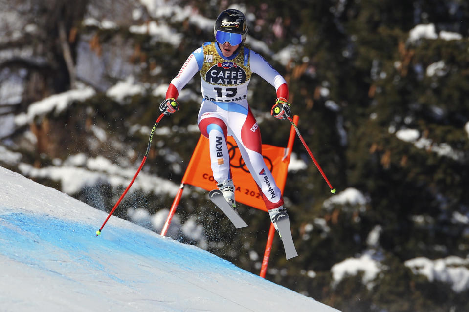 Switzerland's Lara Gut-Behrami takes a jump as she speeds down the course during the women's downhill, at the alpine ski World Championships in Cortina d'Ampezzo, Italy, Saturday, Feb.13, 2021. (AP Photo/Marco Trovati)