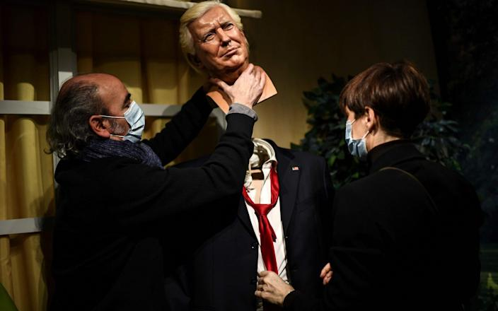 Grevin wax museum employees remove the head of a wax statue of outgoing US President Donald Trump as the statue is taken away from the display area at the Grevin museum in Paris - Christophe Archambault/AFP