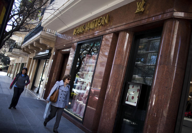 In this Sept. 26, 2012 photo, a woman walks by Louis Vuitton store at the Alvear Avenue, in Recoleta neighborhood in Buenos Aires, Argentina. The world's most luxurious designer brands are abandoning Argentina rather than complying with tight new government economic restrictions, leaving empty shelves and storefronts along the capital's elegant Alvear Avenue, where tourists once flocked to see the latest in fashion. (AP Photo/Natacha Pisarenko)