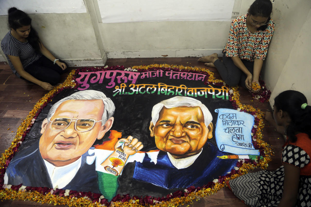 Students from an art school place flower petals around a painting of former Indian prime minister Atal Bihari Vajpayee in Mumbai, India, Thursday, Aug. 16, 2018. Vajpayee, who pursued both nuclear weapons and peace talks with Pakistan, died Thursday at age 93. (AP Photo/Rajanish Kakade)