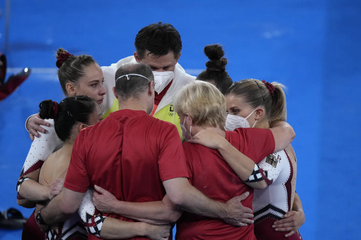 Team Germany huddles together after performing in the women's artistic gymnastic qualifications at the 2020 Summer Olympics, Sunday, July 25, 2021, in Tokyo. (AP Photo/Gregory Bull)