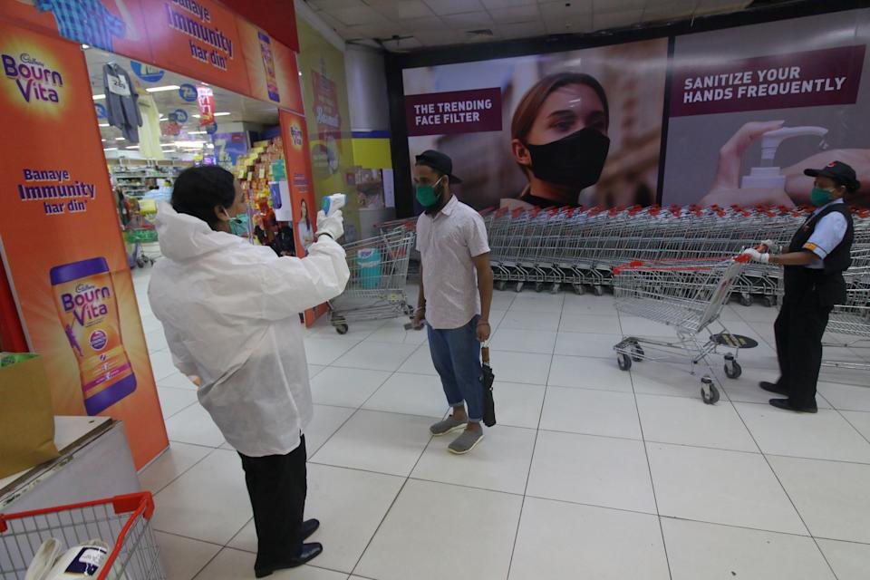 A man wearing a protective face mask has his temperature checked before entering a shop inside a shopping mall after it reopened in Mumbai, India on August 05, 2020. (Photo by Himanshu Bhatt/NurPhoto via Getty Images)