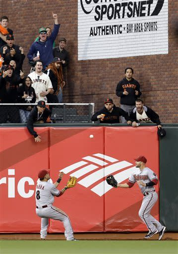 Arizona Diamondbacks center fielder Gerardo Parra, left, and right fielder Cody Ross reach for a fly ball which bounced off the outfield wall on a double by San Francisco Giants' Buster Posey during the first inning of a baseball game on Monday, April 22, 2013 in San Francisco. (AP Photo/Marcio Jose Sanchez)
