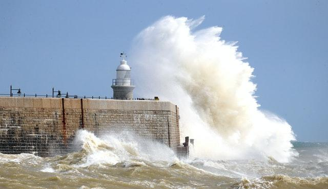 Waves crash over the harbour wall in Folkestone, Kent, on August 21